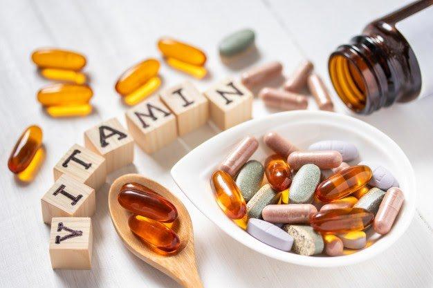 variety-of-vitamin-pills-on-white-wood_43937-361